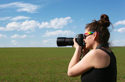 Girl photographer. Girl with big professional camera, take a picture in a beautifully nature background Stock Images