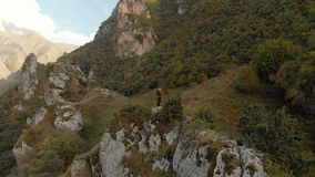 Girl photographer blonde in a hat walks with a camera in the mountains. Chegem gorge North Caucasus stock video footage