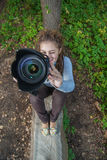 Girl-photographer. Curly girl photographs against summer nature royalty free stock photo
