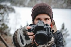 Girl photographer with DSLR camera. Girl photographer in warm clothes looking at camera stock images