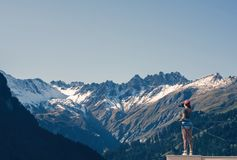 A girl photographer in a red cap with a camera stands on the balcony opposite snow Swiss Alps and forest of national park in Switz Stock Image
