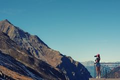 A girl photographer in a red cap with a camera stands on the balcony opposite snow Swiss Alps and forest of national park in Switz Royalty Free Stock Images