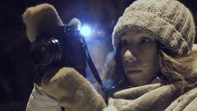 Girl photographer shooting outdoors on snow winter night ligh park.  stock video footage
