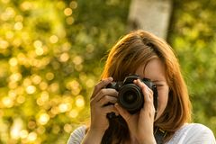 Girl photographer takes pictures against the background of green Stock Photo