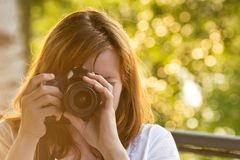 Girl photographer takes pictures against the background of green Royalty Free Stock Image