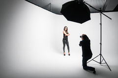 Girl the photographer takes pictures of model in black on a white background. In Studio royalty free stock image