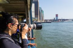 Girl photographer taking photo. Canon camera in hands. New York, NYC, USA- August 26, 2017: Girl photographer taking photo. Canon camera in hands. New York city Royalty Free Stock Photography