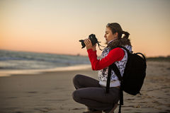 Girl photographer taking pictures with SLR camera Royalty Free Stock Images