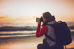 Girl photographer taking pictures with SLR camera Stock Images