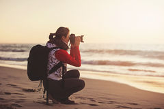 Girl photographer taking pictures with SLR camera Royalty Free Stock Photography