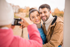 Girl photographing beautiful smiling couple Royalty Free Stock Image
