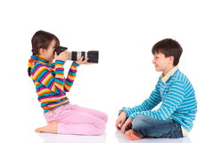 Girl photographing brother Royalty Free Stock Photography