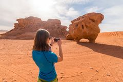 Girl photographing chicken rock in Wadi Rum desert, Middle East, Jordan stock photos
