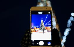 A girl photographing a Christmas tree on a smartphone camera, City, Holidays New Year stock photo