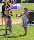 Girl photographing friend with umbrella Royalty Free Stock Photos