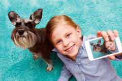 Girl photographing herself and her dog Stock Photography