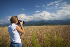 Girl photographing ripe wheat field in bright sun rays Royalty Free Stock Photos
