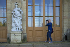 Girl photographing a sculpture at the entrance to the Great Gatchina Palace Stock Photography