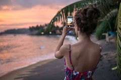 Girl photographing sunset on beach Stock Photography