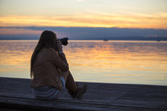 Girl photographing sunset Stock Image