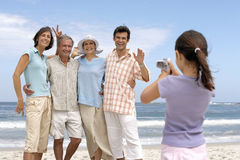 Girl (7-9) photographing three generation family on beach, posing and smiling, sea in background Stock Photos