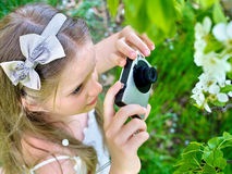 Girl photographs blossoming tree Royalty Free Stock Image