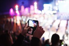 A girl photographs a bright event on her smartphone royalty free stock photography