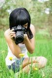The girl photographs a dandelion Stock Photo