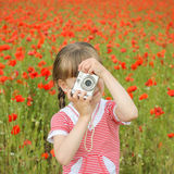 Girl photographs field with poppies.  Royalty Free Stock Images