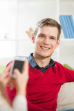 Girl photographs her boyfriend in the living room. Stock Photography