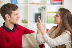 Girl photographs her boyfriend in the living room. Royalty Free Stock Photos