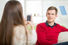 Girl photographs her boyfriend in the living room. Royalty Free Stock Image