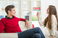 Girl photographs her boyfriend in the living room. Royalty Free Stock Images