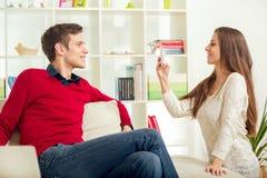Girl photographs her boyfriend in the living room. Stock Photos