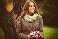 Girl photographs in the park and holding a retro camera Royalty Free Stock Photography