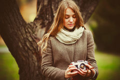 Girl photographs in the park and holding a retro camera Stock Photos