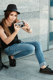 Girl  photographs with retro styled digital camera. Royalty Free Stock Photo