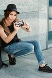 Girl  photographs with retro styled digital camera. Royalty Free Stock Photo