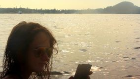 Girl photographs selfie on the beach at sunset. Time stock video