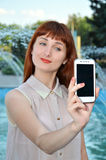 Girl photographs on your mobile phone. The girl photographed on white smartphone Royalty Free Stock Image