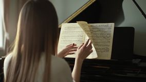 Girl pianist with hands turn over musical notes close up in slow motion. Woman pianist turns over musical notes while sitting back to camera close up in slow stock video