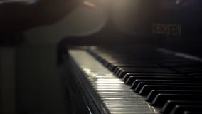 Pianists hand opens grand piano and starts playing music close up in slow motion. Girl pianists two hand opens the grand piano and starts playing gentle stock video footage