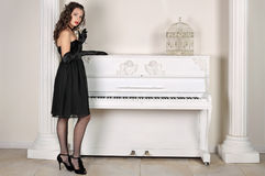 The girl about the piano. The beautiful girl in an evening dress stand about the white piano Stock Photo