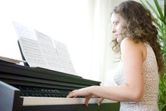 Girl on the piano. A girl playing the piano stock photography