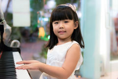 Girl at piano. Happy little Asian girl is playing piano Royalty Free Stock Photo