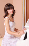 Girl with piano. Beautiful young girl with piano Stock Images