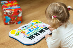 Girl with piano toy. Pretty little girl playing with a piano toy Royalty Free Stock Images