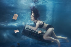 Girl with piano under water. Royalty Free Stock Image