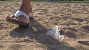 Girl pick up plastic trash at the child`s playground or sandy beach.