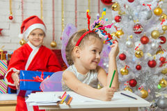 The girl picked up a toy fireworks on the head, Santa Claus sitting behind her Royalty Free Stock Photo